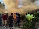 Anonymní zachránce vyná�í z ho�ícího domu v americkém Fresnu star�ího mu�e,...