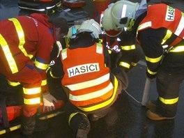 Záchranáři s hasiči ošetřují jedenáctiletého cyklistu. (22. října 2014)