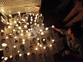 Lidé zapalují svíčky u portrétů 43 studentů, kteří zmizeli 26. září (Monterrey, 23. října 2014).