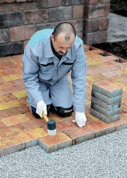 Dlažební bloky se usazují jeden po druhém na ložní vrstvu pomocí bílé gumové...