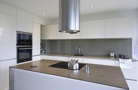 Kuchyň ve smetanové barvě splývá se stěnou, barevně ji příjemně doplňuje pracovní deska z umělého kamene.