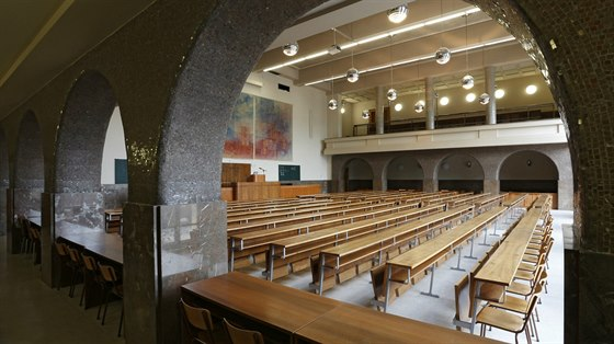 Krása v detailech. Loubí v největší aule fakulty zdobí drobná kamenná mozaika, která tlumeně odráží světlo. Při pohledu zvenku se místnost skrývá za velkými okny nad balkonem, který měly podpírat čtyři sochy.