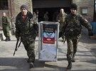 Ozbrojenci přenášejí volební urnu k provizornímu hlasovacímu místo nedaleko...