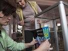 Členky volební komise v Doněcku přelepují na volební urně ukrajinský státní...