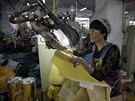 Pracovnice americké firmy šije v čínské provincii Šan-tung obleky, které budou chránit zdravotníky před ebolou (30. října 2014).