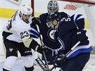 Ondřej Pavelec hlídá branku Winnipegu, usadil se před ním Steve Downie z Pittsburghu.