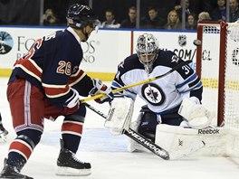 Brankář Winnipegu Ondřej Pavelec čelí šanci Martina St. Louise z New York