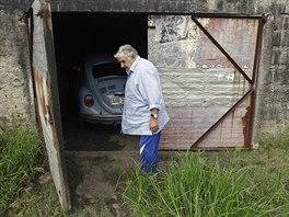 Uruguayský prezident Mujica před svou garáží na okraji Montevidea, kde má ustájený bleděmodrý volkswagen brouk z roku 1987.