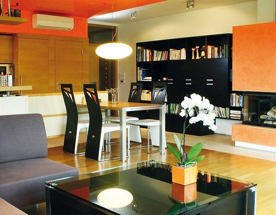 Společenská část domu s odpočivním koutem, jídelním stolem a knihovnou, vše ve vzájemné barevné, tvarové a materiálové kompozici.