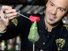 Matthias Giroud dekoruje drink s pomocí velké pinzety.
