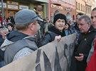 Dva mladé lidi s transparentem Stydím se za svého prezidenta brzy odvedli policisté v civilu. (11. listopadu 2014)
