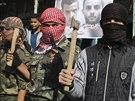 V Rafáhu maskovaní palestinští bojovníci se sekerami, noži a zbraněmi oslavují útok na židovské věřící v jeruzalémské synagoze.