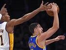 Klay Thompson (vpravo) z Golden State se pokouší zakončit, o blok se snaží Wesley Johnson z LA Lakers.
