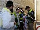 Záchranáři prohlížejí zakrvácený modlitební šál ze synagogy v jeruzalémské čtvrti Har Nof (Izrael, 18. listopadu 2014).