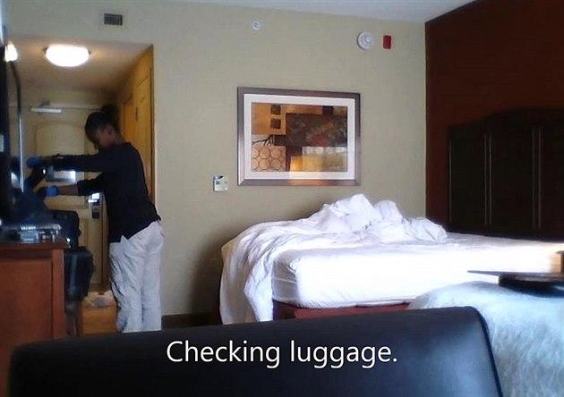 Pokojská prohlí�í kufr hotelového hosta.