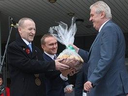 Starosta Kopřivnice Josef Jalůvka předává Miloši Zemanovi kopřivnickou specialitu - klobásníky. (12. listopadu 2014)