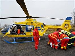 Z�chran��i s pomoc� hasi�� p�enesli zran�n� do vrtuln�ku, kter� pacienty transportoval do Pop�leninov�ho centra Fakultn� nemocnice Ostrava. (18. listopadu 2014)