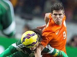 Klaas Jan Huntelaar z Nizozemska (vpravo) bojuje o míč s mexickým kapitánem Andresem Guardadem.