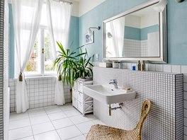 Koupelna si svůj bílý kabátek z mozaiky a čtvercových obkládaček pořídila ve slevovém výprodeji.