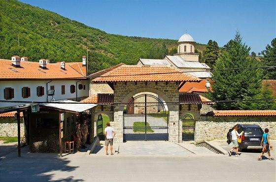 Při příjezdu na parkoviště u kláštera Visoki Dečani projíždíme kolem opevněného vojenského stanoviště a i před bránou stojí strážní budka.