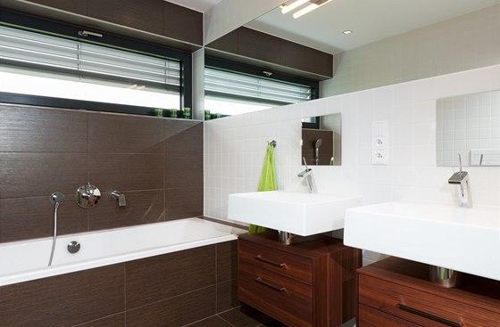 Kombinace velkoformátových obkladů 20 × 60 cm s dekorem dřeva a velké mozaiky 5 × 5 cm v bílé barvě je nadčasová.