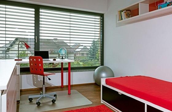 Dřevěnou podlahu chrání před kolečky pracovní židle v pokoji školáka plastová podložka.