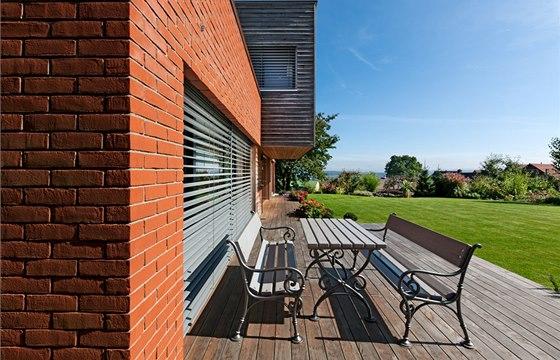 Dřevo na terase a fasádě získává příjemnou patinu, výhled do zahrady a okolí se majitelům jen těžko omrzí.