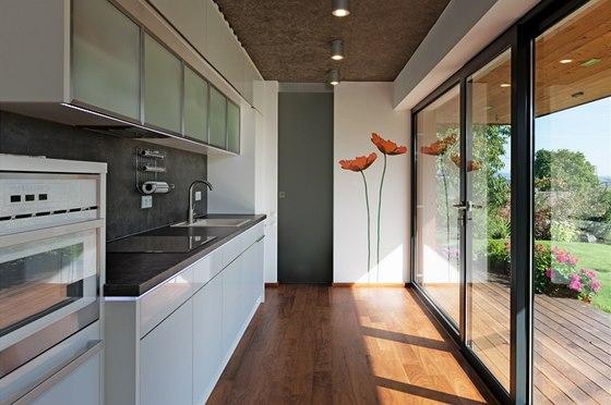 Kuchyňská linka je zabudovaná v nice a navíc zapuštěná 15 centimetrů do zdi tak, aby působila subtilněji.