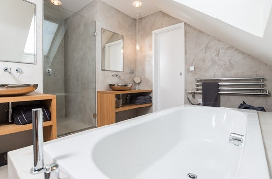 Na středu proti vaně je do vysoké části pod šikmou střechou umístěný sprchový box.