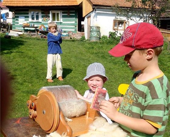 V Semilech si děti kolem roubenky zkoušejí různé tradiční práce. Třeba i  zpracování ovčí vlny.