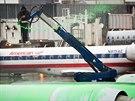 Pracovník letiště stříká rozmrazovací tekutinu na letadlo společnosti Eagle jet v New Yorku. (26. listopadu 2014)
