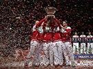 Švýcarští tenisté v euforii třímají trofej pro vítěze Davis Cupu. V pozadí stojí téměř jako čestná stráž tým poražené Francie.