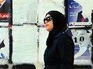 Žena prochází kolem volebních plakátu, v neděli Tunisané volí prezidenta (21. listopadu 2014).