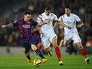Lionel Messi (vlevo) upaluje s míčem, stíhá ho Grzegorz Krychowiak ze Sevilly