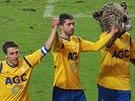 Tepličtí fotbalisté Jan Krob (vlevo) a Alen Melunovič slaví výhru nad Duklou spolu s maskotem.