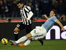 Stefan De Vrij (vpravo) chce skluzem zastavit útočný výpad Carlose Téveze z Juventusu Turín.