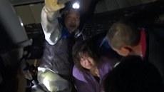 Záchraná�i vytahují �enu z domu po�kozeného zem�t�esením. (23. listopadu 2014)