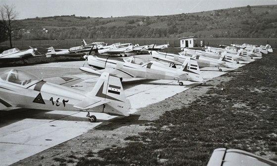 """Zajímavá fotka letadel z Otrokovic. V řadě na betonové ploše vidíme odpředu 5 strojů Z-526FI pro Irák (proto to """"I"""" v označení), první s trojúhelníkovými výsostnými znaky a číslem 943 na trupu je učen vojenskému letectvu, následují 4 kusy pro """"civilního"""" uživatele. Že verze 526FI byla úpravou nouzovou, prozrazuje lomená horní linie trupu před kabinou. Celkem bylo vyrobeno 15 těchto letadel. Zajímavostí je také z jakéhosi důvodu nesprávné typové označení Z-526AF na směrovce, které již patřilo """"normální"""" jednomístné verzi."""