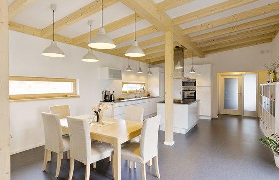 Společná část domu. Hřejivý tón v jinak chladném šedobílém prostoru obstarává jídelní sestava z masivního dřeva, vnitřní rámy oken a dveří na terasu a především trámoví stropu.
