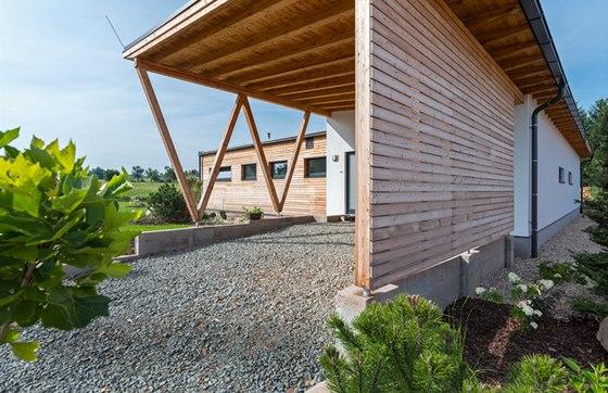 Z přístupové strany dotváří dům kryté stání pro vozidlo s nosnými sloupy ve tvaru písmene W. Šikmé linie sloupů vnášejí do jednoduché pravoúhlé hmoty dynamiku a odlišují stavbu nezaměnitelným podpisem.