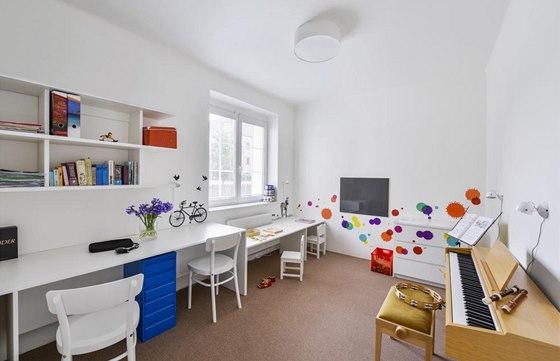Místnost v přízemí domku sousedící přímo s otevřenou kuchyní, jídelnou a obývacím prostorem slouží jako pracovna rodičů a herna děvčat. Je vybavena praktickým nábytkem zhotoveným na míru a vtipně oživena veselými samolepkami.