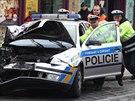 Policisté pomáhají odklidit svůj vůz, který boural na pražském Újezdě (9.12.2014)