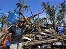 Jeden z obyvatel filip�nsk�ho Boronganu na ostrov� Samar p�in�� plynovou lahev k provizorn�mu va�en�. Mnoho dom� tajfun zcela srovnal se zem� (8. prosince 2014).