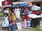 Filipínci čekají na příjezd evakuačního vozu, který je má dopravit do některého z bezpečných úkrytů (4. prosince 2014)