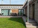 Barevné ladění interiéru se propisuje i do vnější fasády. Bílá omítka podlouhlé společenské části s pultovou střechou dobře koresponduje s laťovým modřínovým obložením části klidové, jež s obytným ramenem domu svírá pravý úhel.