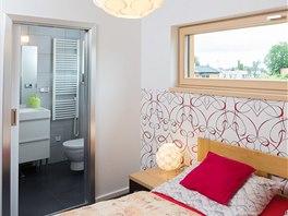 Ložnice rodičů nemá přímý výstup na terasu (ten raději dopřáli dětem), ale jen horizontální okno. Zato je vybavena vlastní koupelnou přístupnou posuvnými dveřmi.