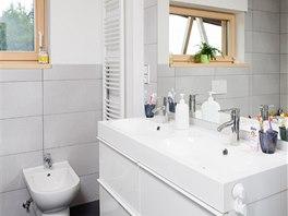 """""""Hlavní"""" koupelna s bíle lakovaným nábytkem, velkoformátovým bílým obkladem a tmavě šedou dlažbou dodržuje estetický a materiálový koncept celého interiéru."""