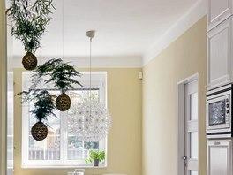 Otevřený prostor mezi jídelnou a obývacím pokojem zdobí zavěšené květiny, takzvané kokedamy.
