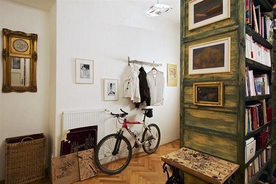 Dřevěná, nazeleno mořená knihovna je praktickým úložným prvkem a zároveň rozděluje velký prostor vstupní haly.