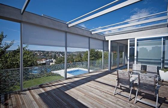 Terasa s dřevěnou palubou z tropického dřeva přímo navazuje na zimní zahradu a slouží jako letní obývák. Po venkovním schodišti lze sejít z terasy kolem garáže na zahradu k bazénu.